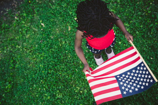 African-American Girl in Red, White and Blue USA Flag Outfit Holding A USA Flag