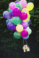 A flying yellow wooden house hanging from a bundle pastel colored balloons