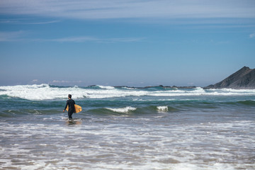 surfer walking into ocean with his surfboard