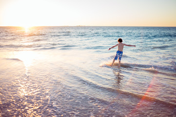 Child riding a skim board at the beach at sunset