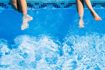 Legs of young women in the water of a swimming pool during a sunny day
