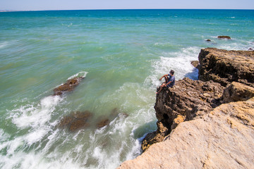 Brave man enjoy watches the ocean on top of the end of the cliff, rock in beautiful rock beach. summer vocation concept