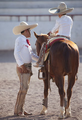 Mexican Guacho teaching boy to ride.