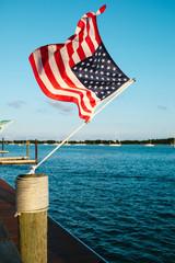American flag tied with rope on bollard waving in air against sky