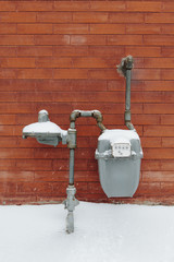 Gas utility meter and fresh snow outside brick building