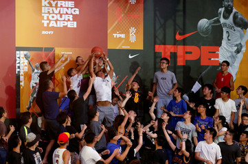 Fans jump for a ball throwing by NBA player Kyrie Irving of the Cleveland Cavaliers during a promotional event in Taipei
