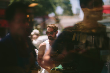 A reflection of a young man walking through the crowd