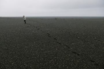 Man Walking Alone Through S��__lheimasandur_��_��_s Black Sandy Beach