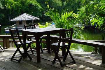 open tropical restaurant table and chairs near natural water