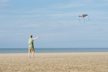 Man flying dragon kite on the beach