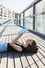 Young beautiful student woman reading a book lying on a wooden floor.