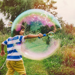 Cute little boy creating huge bubble from a bubble wand in the nature