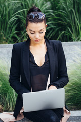 Business woman using her laptop outdoors