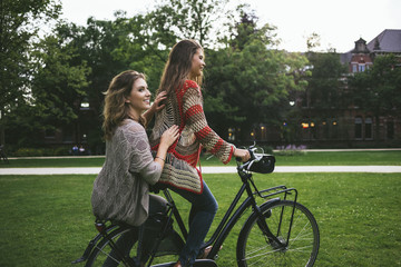 Young female friends on the bicycle in Amsterdam