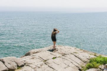 girl in hat on rocks overlooking the ocean