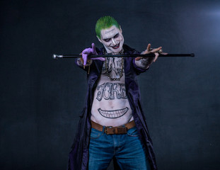 Grim evil character with drawings on the body keeps the stick. green hair