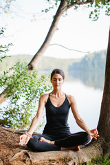 Beautiful woman practicing yoga by a lake