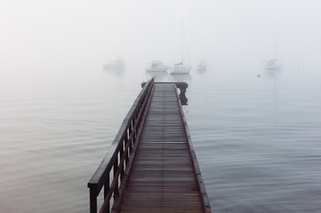 Wooden jetty stretching out onto a river with moored yachts just visible in dense fog