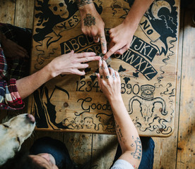 Seance hands joined on a Ouija board