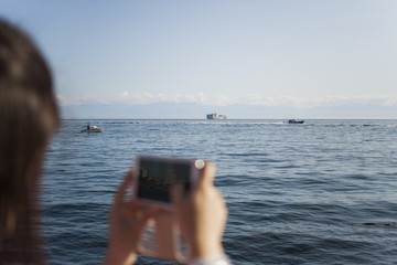 Woman taking ocean pictures with her smartphone