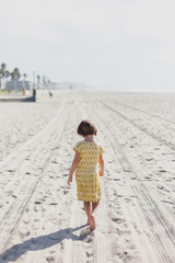 Girl wearing yellow dress walking along empty beach