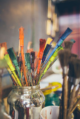 Used paintbrushes and utensils in a glass on a table