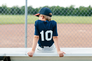 Young baseball player sitting on the bench