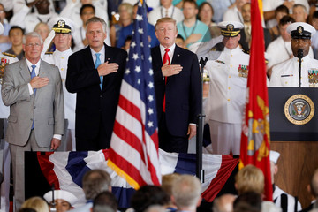 U.S. President Donald Trump, flanked by Virginia Governor Terry McAuliffe, sings the national anthem as he participates in the commissioning ceremony of the aircraft carrier USS Gerald R. Ford at Naval Station Norfolk in Norfolk