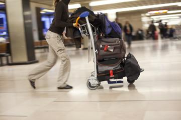 femme qui pousse un chariot de bagages en courant à l'aéroport