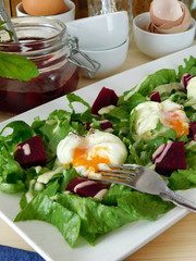 Open poached egg on a green salad and pieces of beetroot