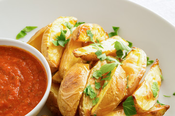 golden roasted potato wedges with tomato sauce