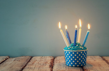 Birthday concept with cupcake and candles on wooden table.