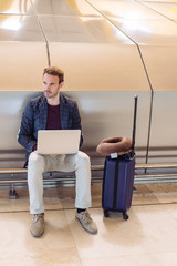 Young attractive man sitting at the airport working with a laptop waiting his flight with a suitcase