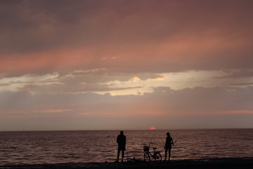 Girl and boy fishing on the sea at sunset