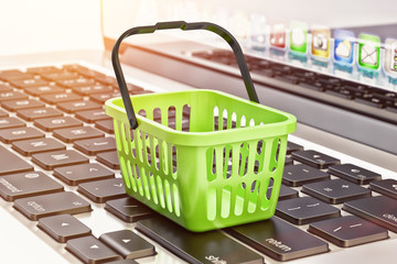 Online shopping, internet purchases and e-commerce concept, green shopping basket on computer laptop keyboard