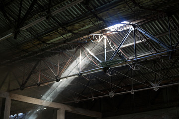 light beams protruding from old factory ceiling