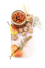 Pear jam, pears and walnuts on a light pink tray on a white background top view..
