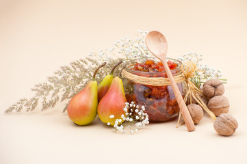 Still life with pear jam, pears, dried herbs and walnuts on a light beige background..