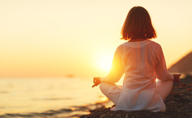Fototapete - woman practices yoga and meditates in lotus position on sunset beach