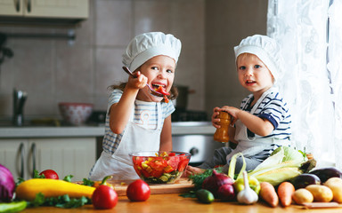 Healthy eating. Happy children prepares  vegetable salad in kitchen.