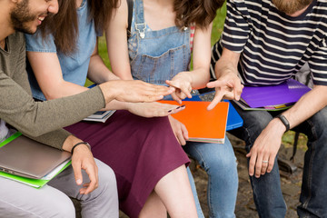 Young students playing Rock Paper Scissors. Students sitting on bench playing games.