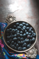 Blueberries in a tin bowl and napkin on slate
