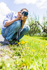 Young man taking pictures of yellow dandelion flowers by road with professional, DSLR camera