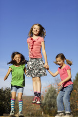 Three happy girls jumping while holding hands