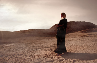 Woman walking in sandy desert in black arabian dress abaya during Ramadan before sunset, photo session in the authentic arabic style, deep clouds sky and mountains picturesque sandy landscape