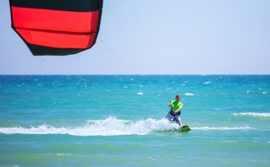 Young man kitesurfing in blue sea