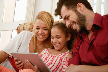 Happy Family Laughing Looking At Video On Tablet Computer