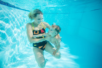 Young woman and little son swimming underwater
