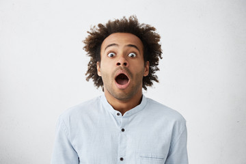 Omg, Wow. Picture of funny emotional dark-skinned male customer in light-blue shirt gaping with wide eyes, shocked with big sale prices on package tour holiday, feeling impatient and excited