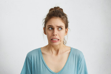 Beautiful woman in casual clothes looking nervously aside feeling distrust or fear while posing against white background. Scared blue-eyed female holding her breath with anticipation of horror